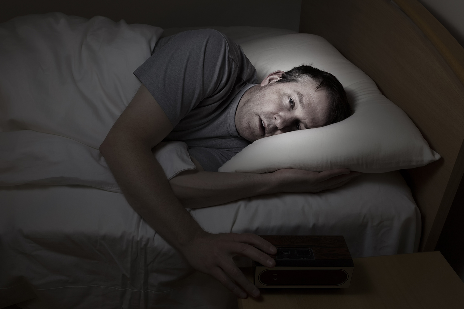 Man lying in bed unable to sleep