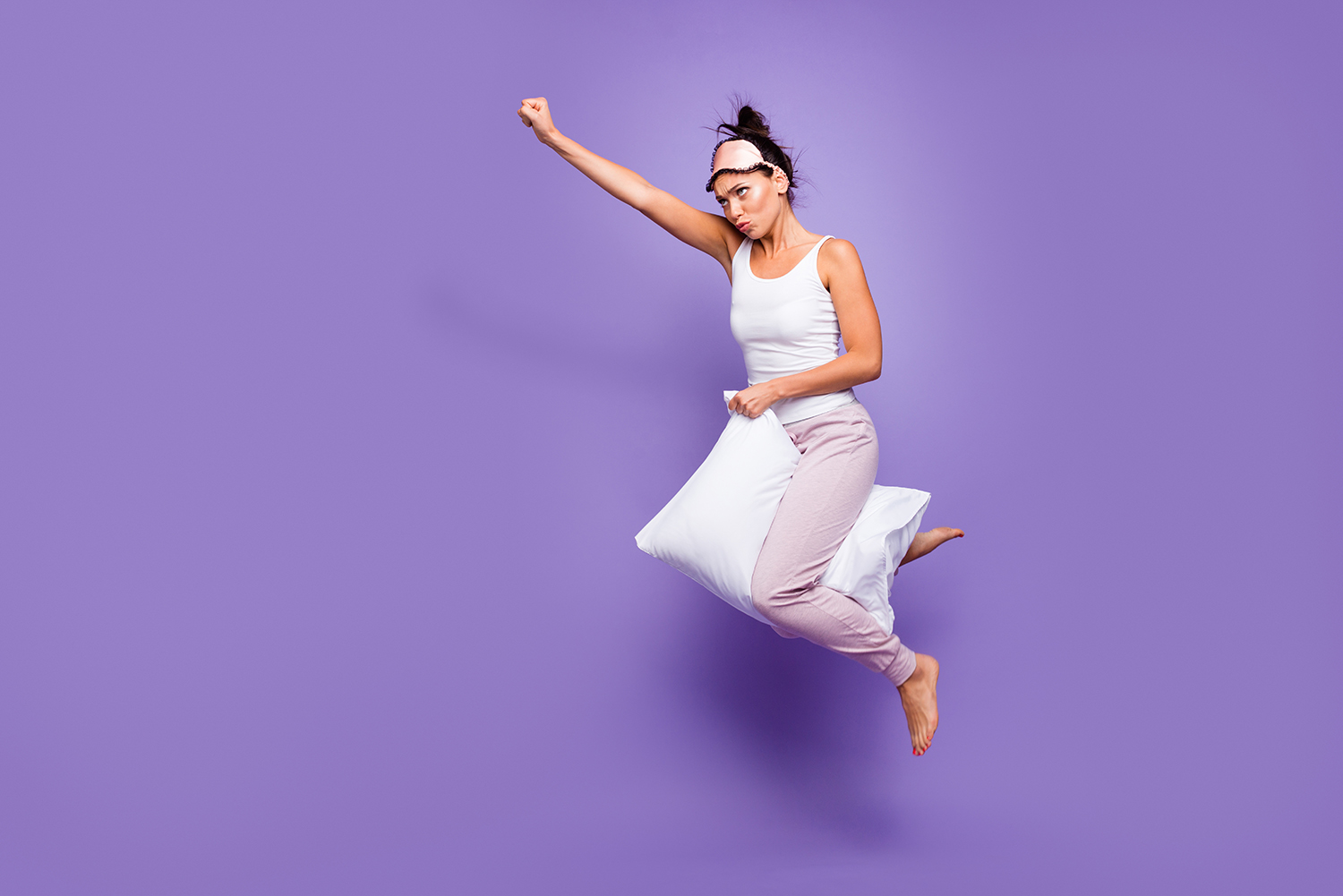 Woman flying through air on pillow